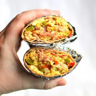 Holding a split in half breakfast burrito.