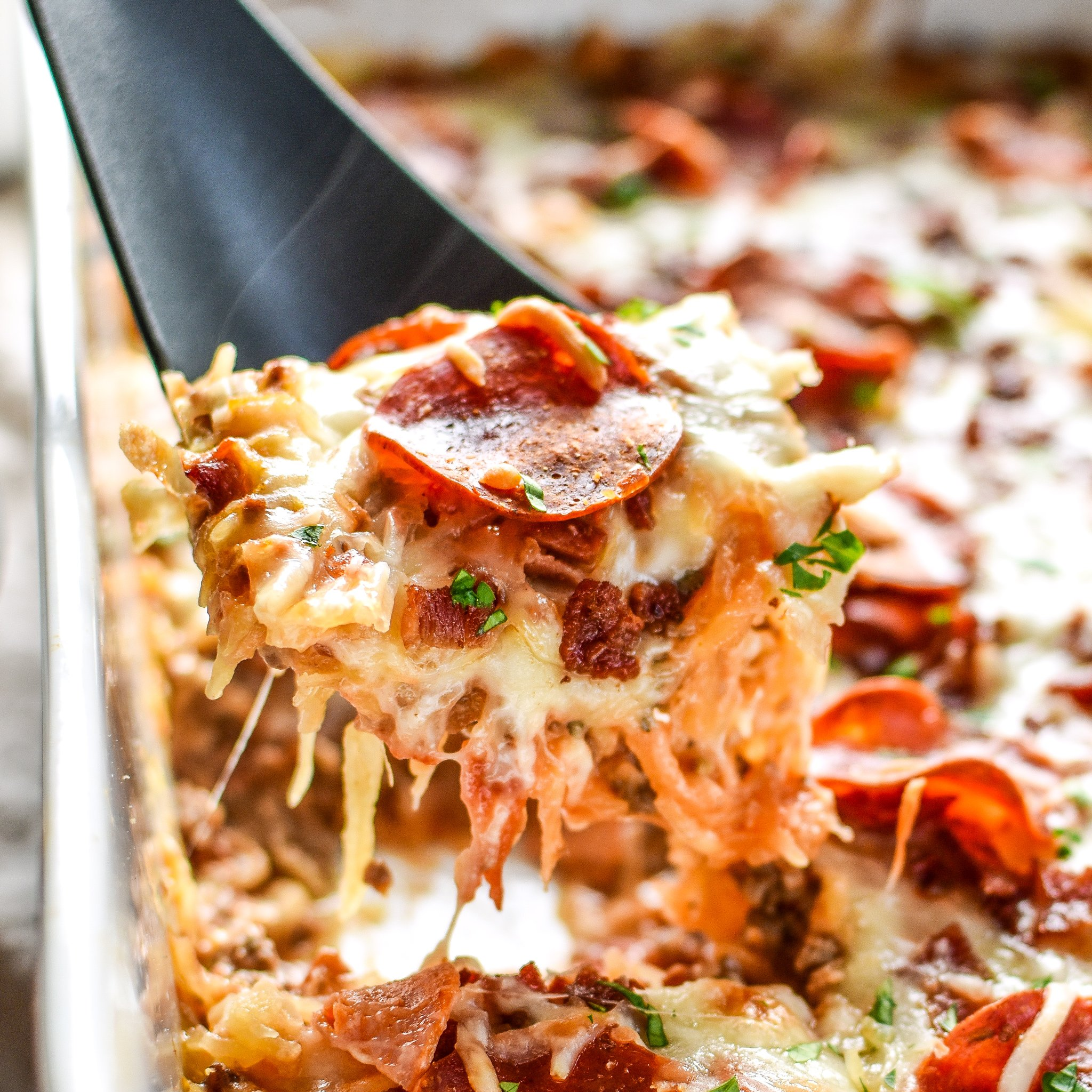 The best shot of Meat Lover's Spaghetti Squash Pizza Casserole - It's pizza, but morphed into a not-that-bad-for-you spaghetti squash casserole with meat lover's toppings! - ProjectMealPlan.com