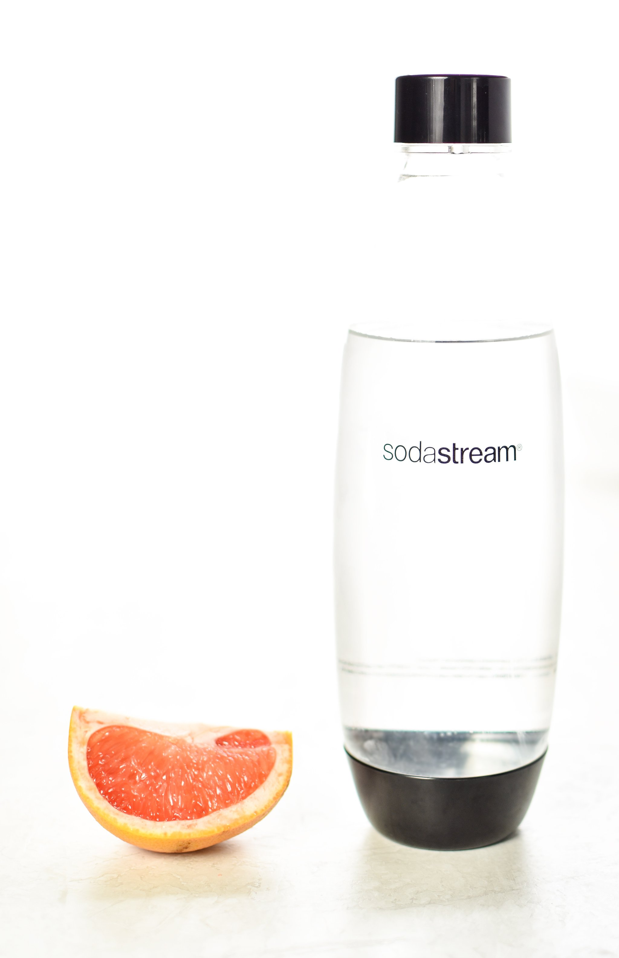 A slice of grapefruit sitting next to a SodaStream carbonating bottle filled with cold water in a bright room.