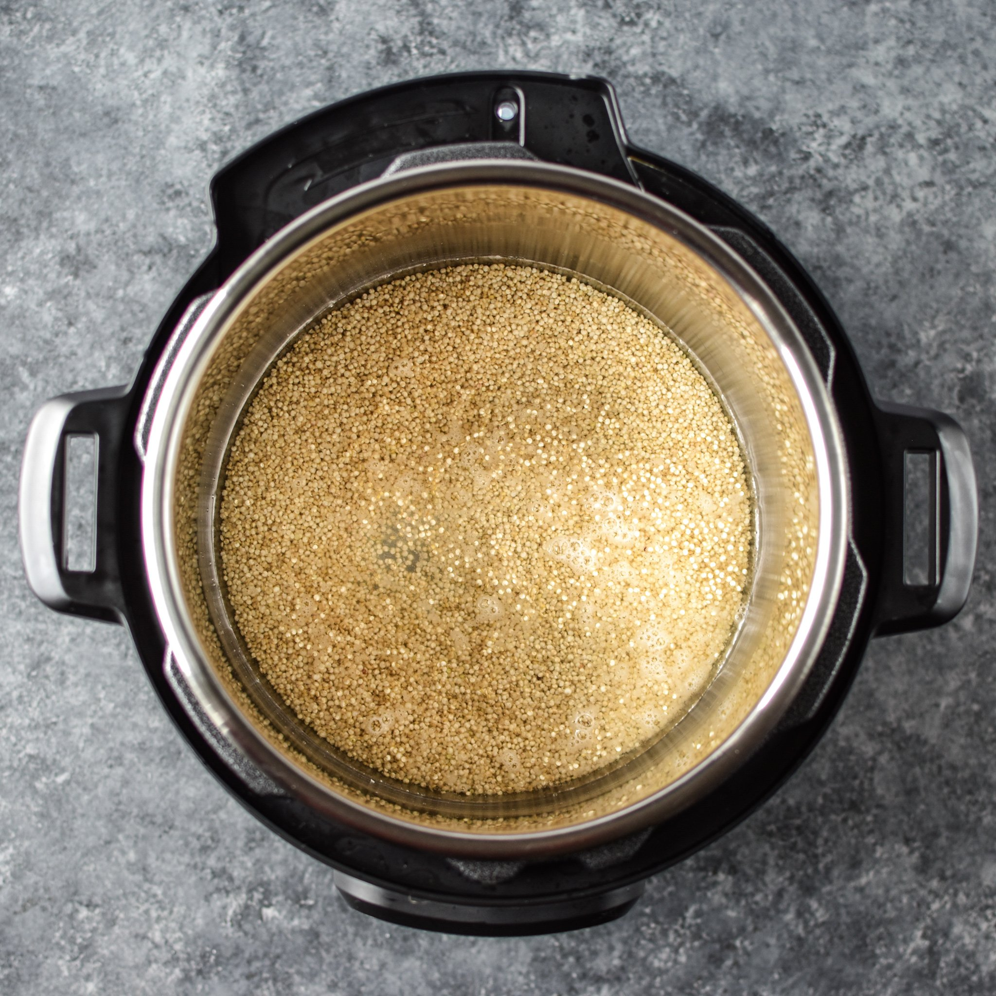 Instant pot with quinoa seen from above, uncooked and ready to be plugged in.