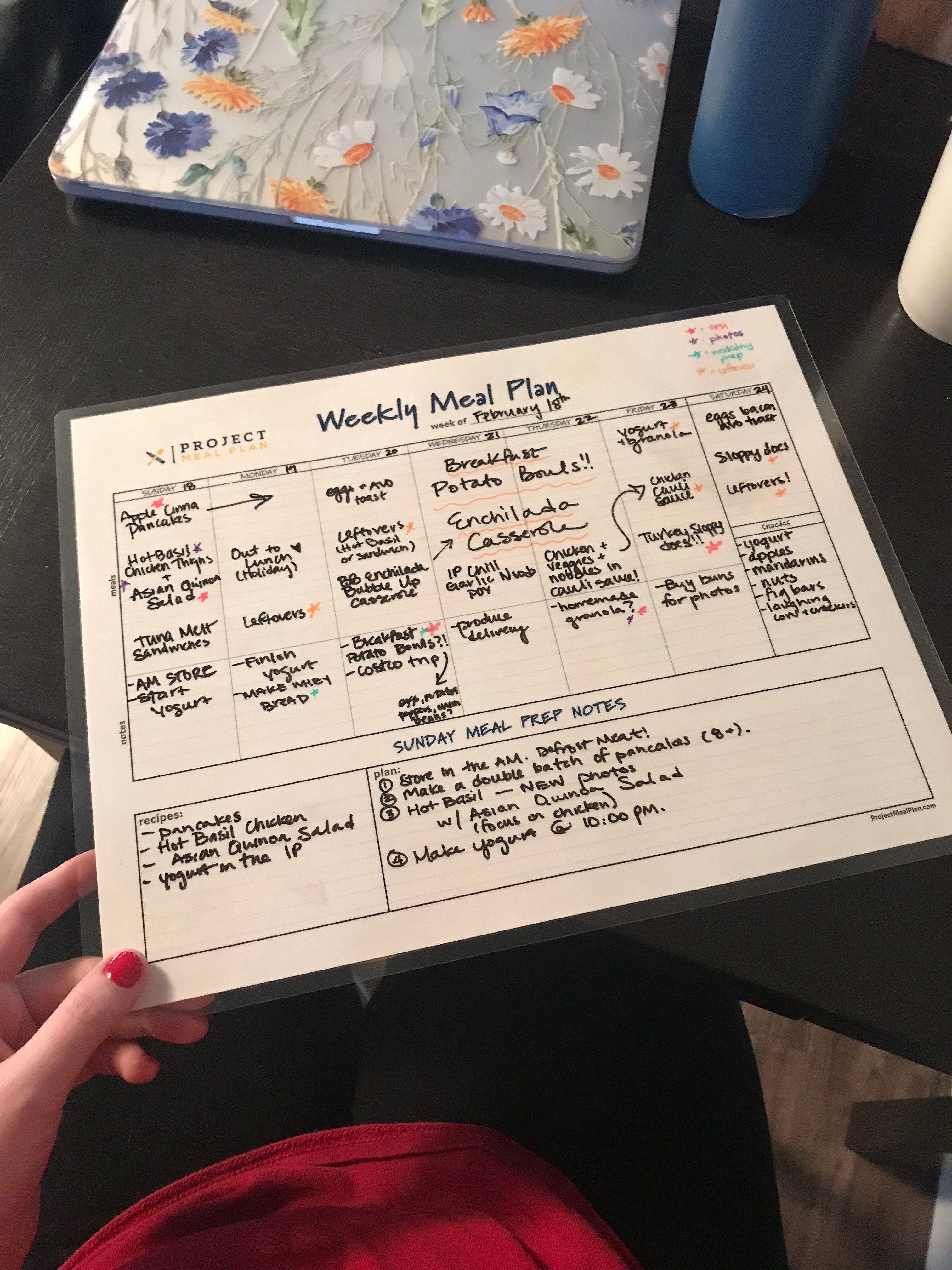 A laminated chart with a handwritten meal plan showing breakfast lunch and dinner for the week of February 18th.