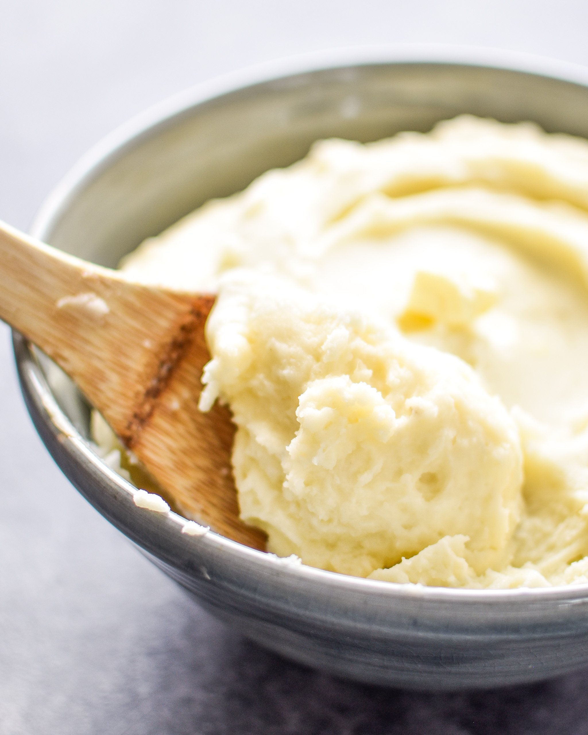 A spoonful of 3-Ingredient Mashed Potatoes resting in a dish of mashed potatoes.