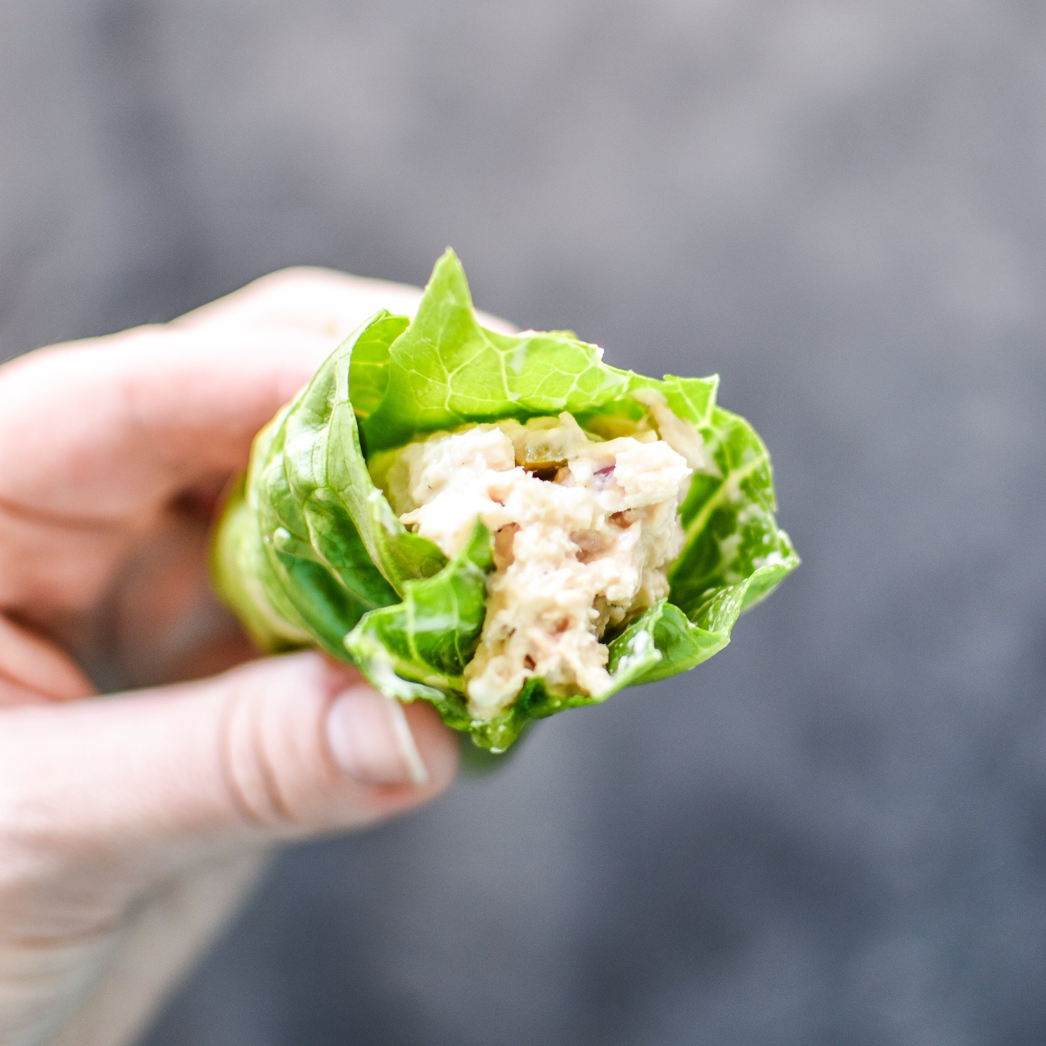 Holding a tuna salad lettuce wrap meal prep item in hand.