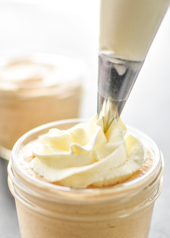 Piping whipped cream on the pumpkin spice whipped greek yogurt.