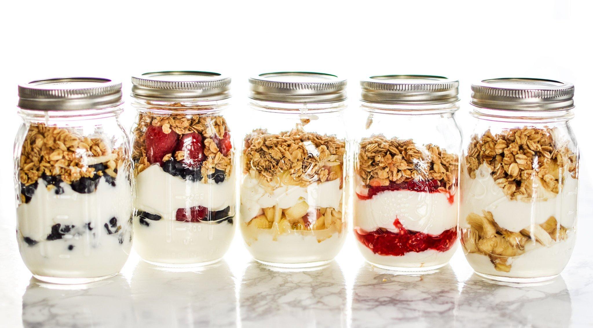 Fruit and greek yogurt parfaits in mason jars.