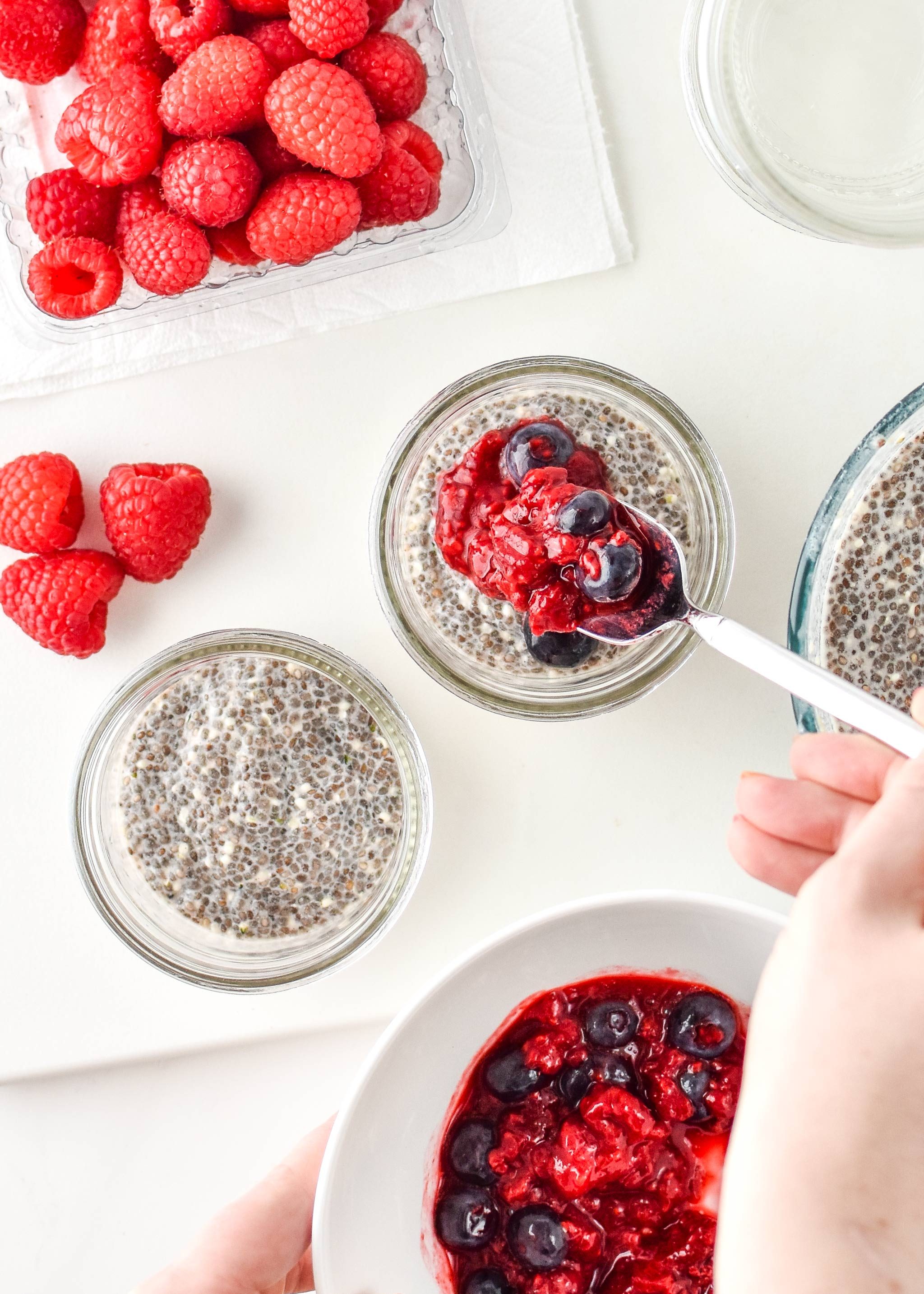 Adding mashed berries to create the chia pudding breakfast parfaits