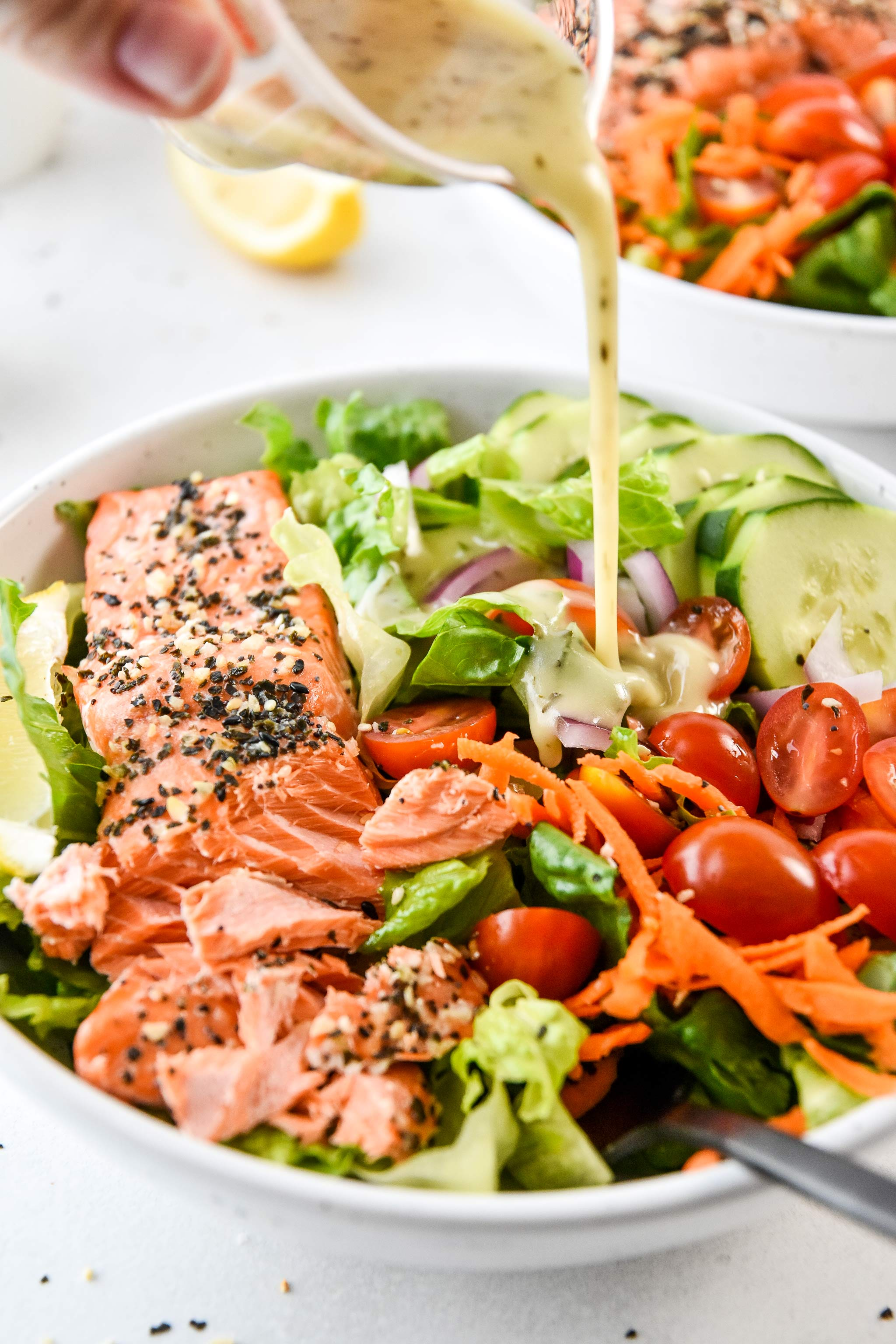 adding dressing to the everything bagel baked salmon salad
