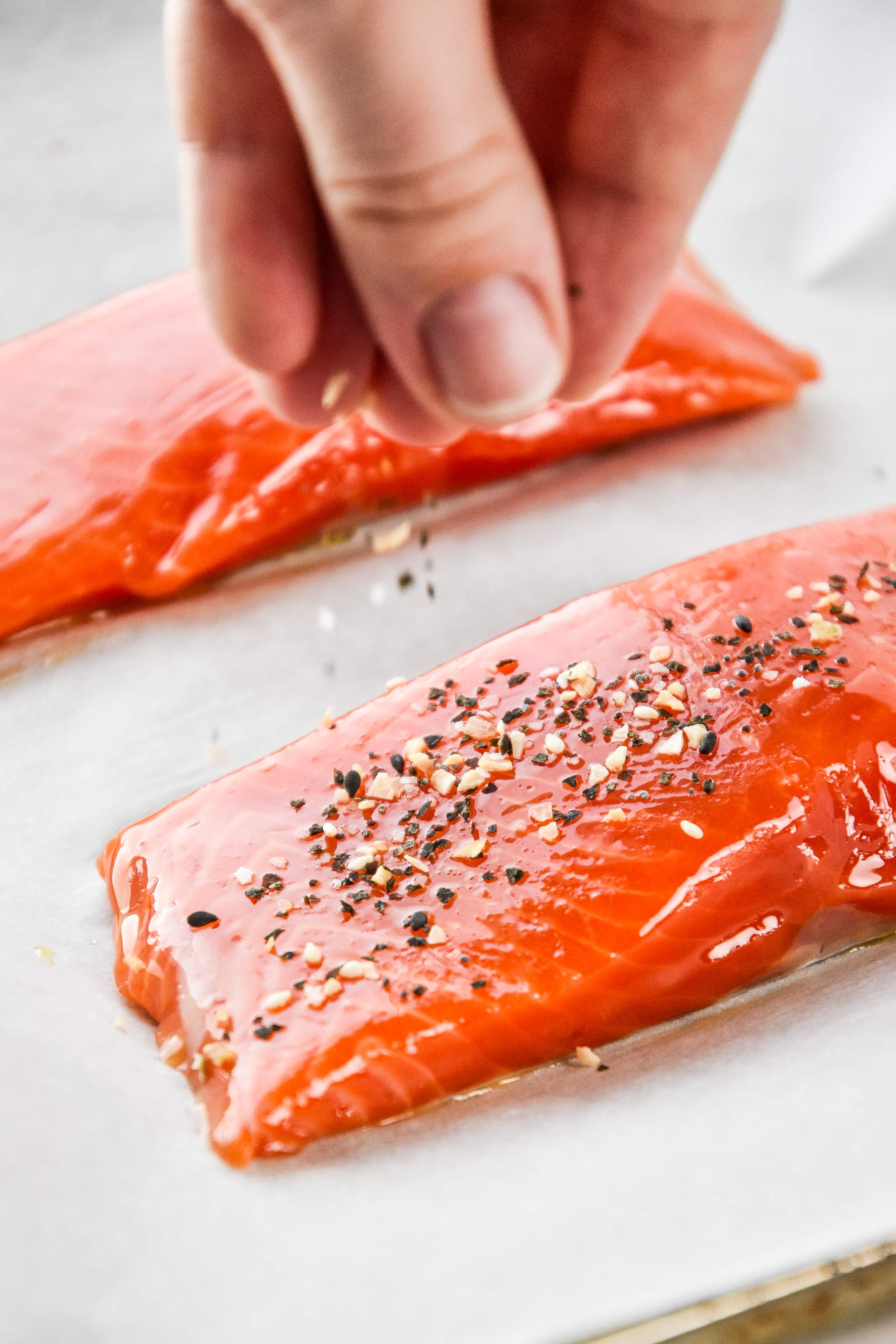 sprinkling everything but the bagel seasoning on the salmon filets