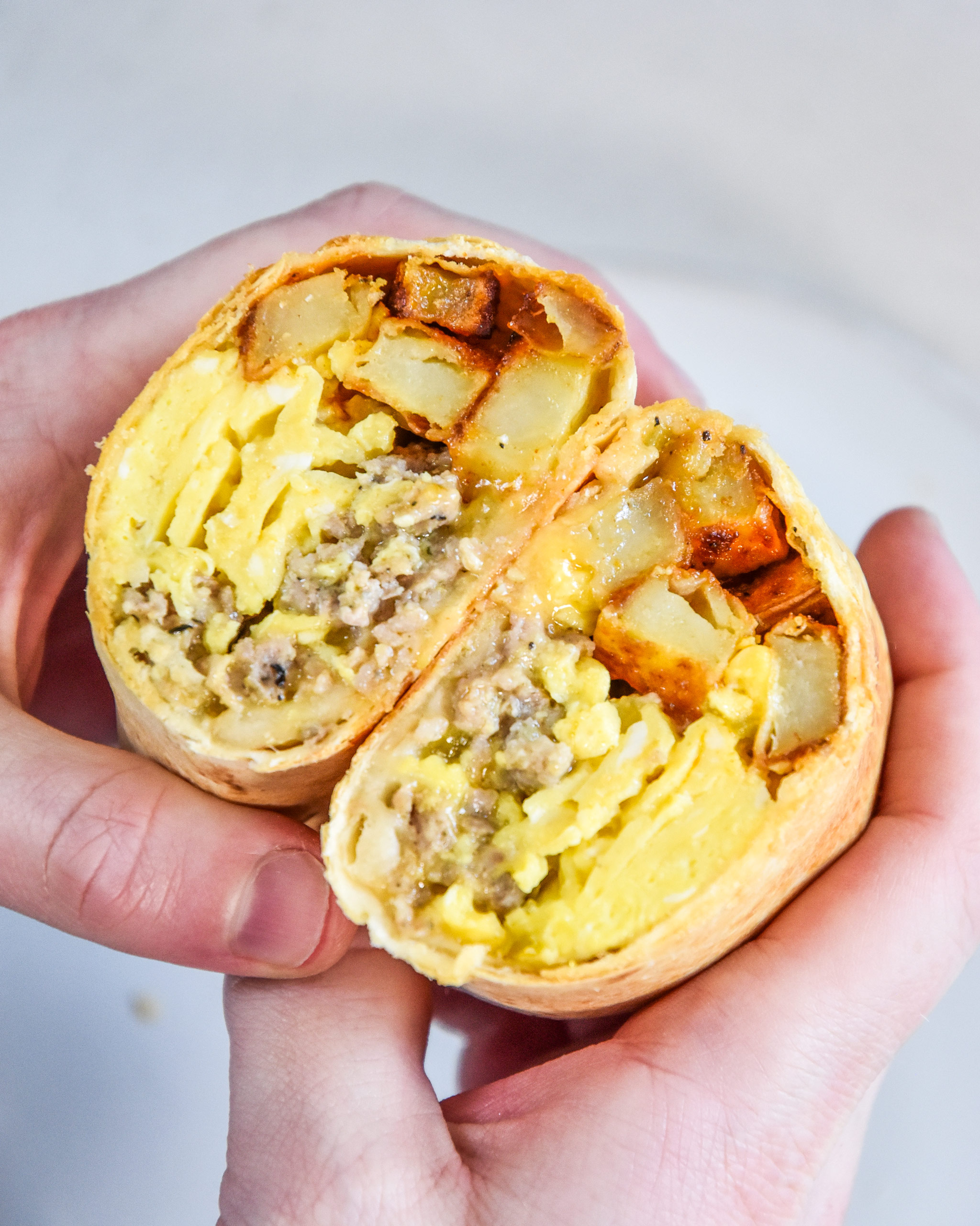 an air fryer breakfast burrito cut in half in someone's hands