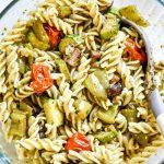 bowl of roasted veggie pesto pasta with a spoon