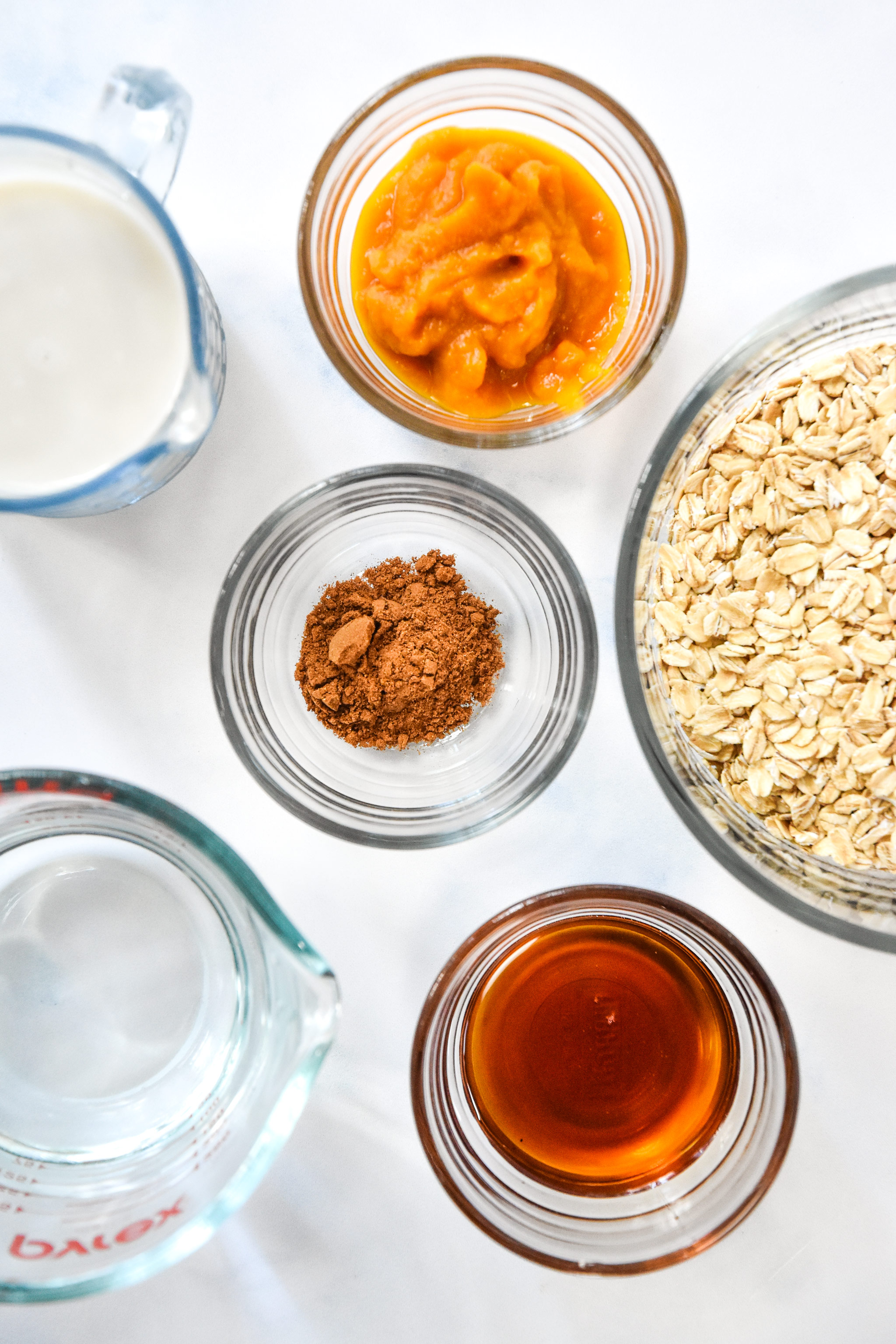 ingredients for the oatmeal including oats, pumpkin puree, and maple syrup.
