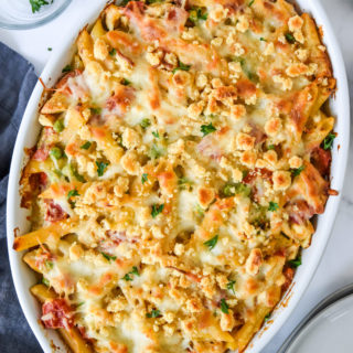 creamy pesto pasta chicken bake fresh from the oven in a white baking dish.