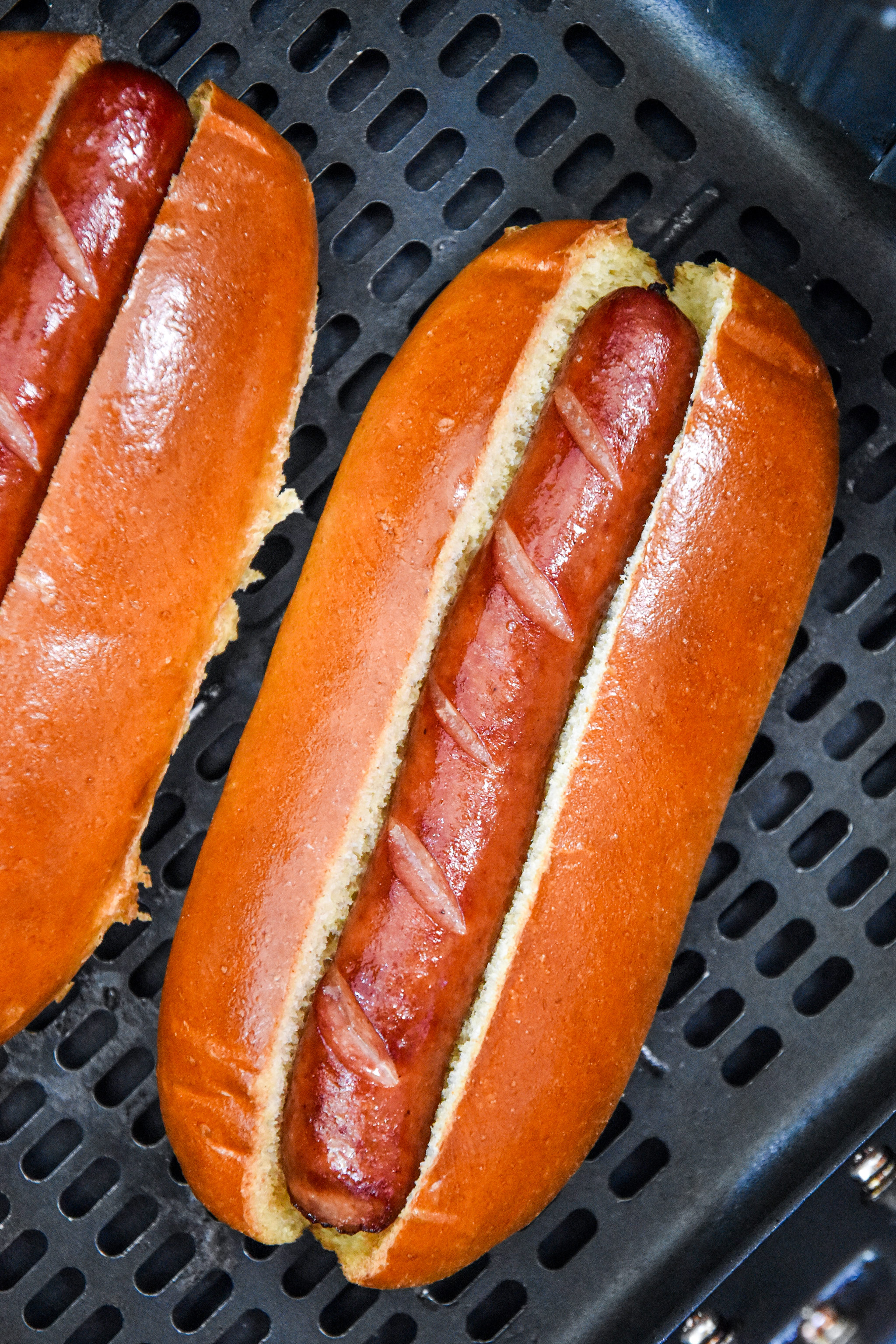 toasted buns and cooked hot dogs in the air fryer basket.