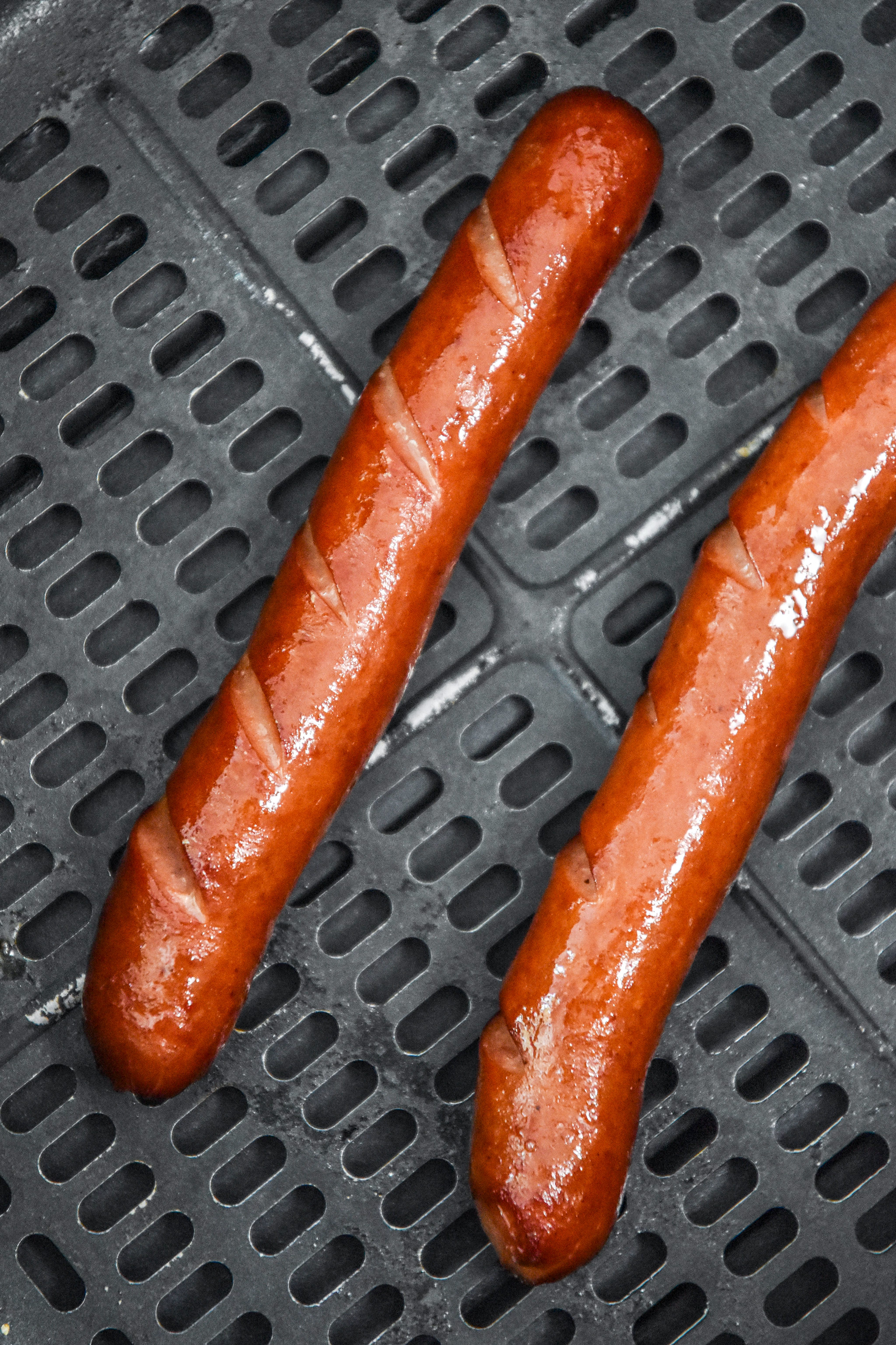 cooked hot dogs in the air fryer basket.
