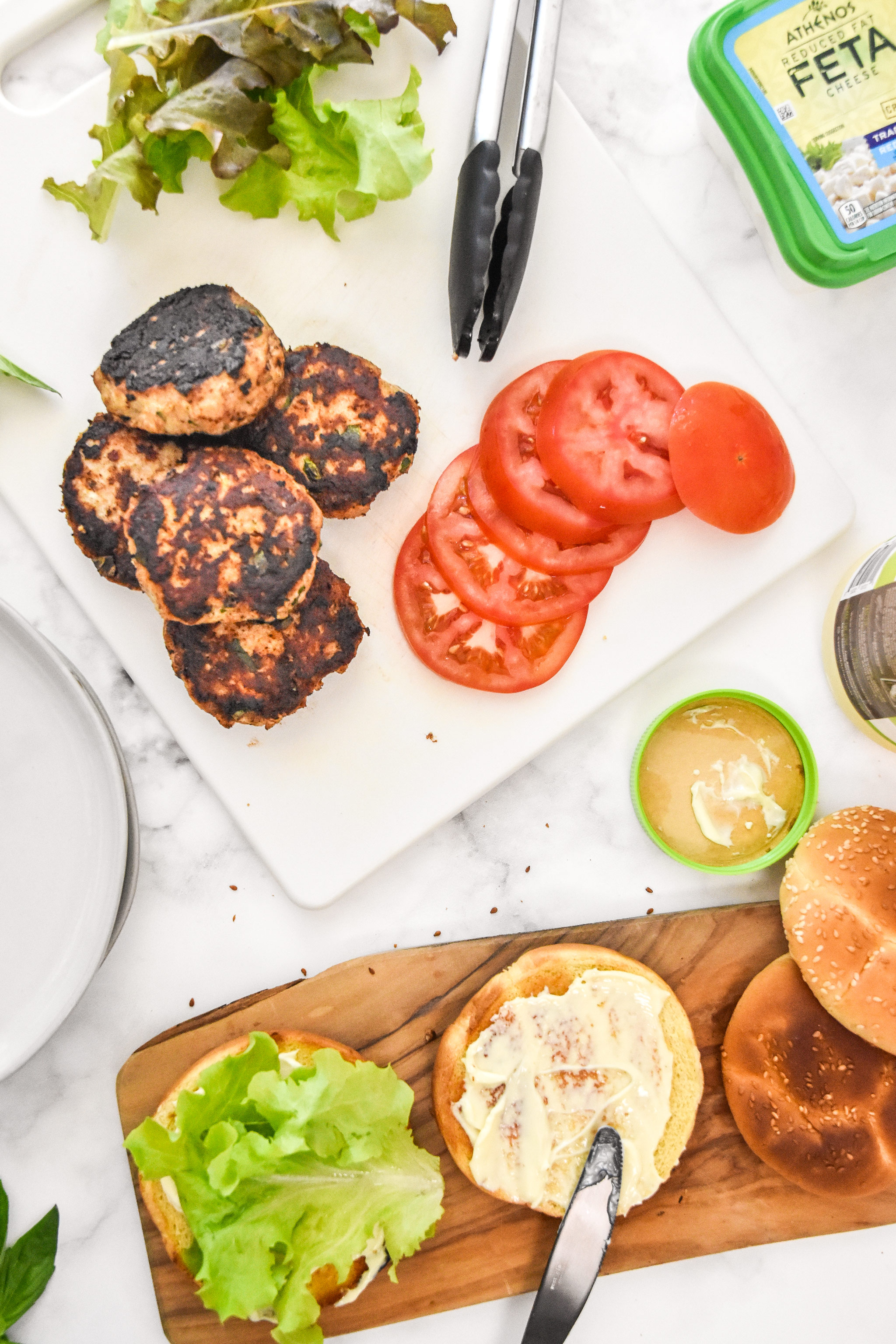 burger toppings, cooked burgers and buns on cutting boards.