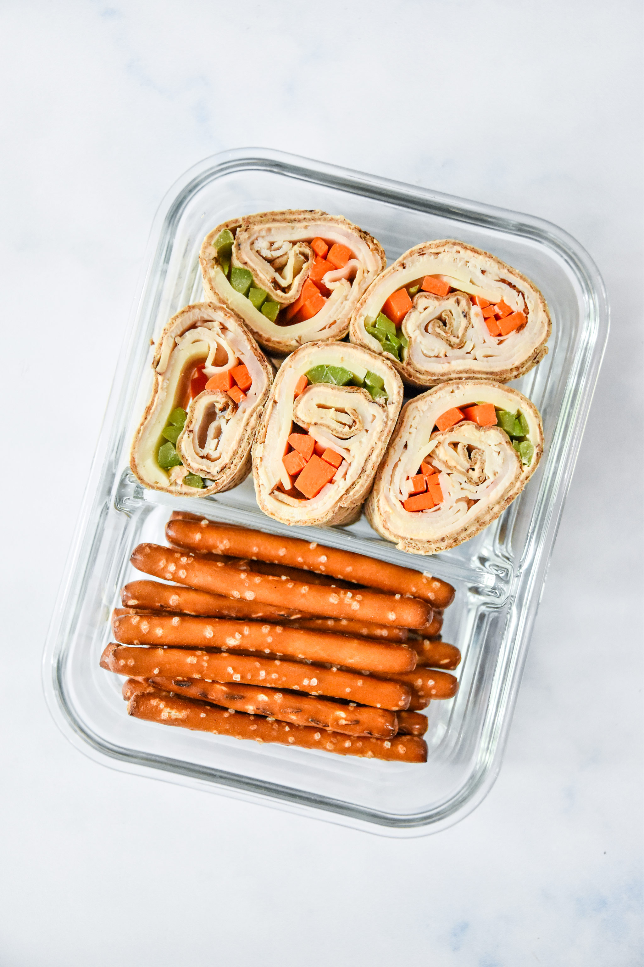 glass container with buffalo chicken pinwheels meal prep and pretzels.