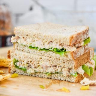 lazy no chop tuna salad sandwich cut in half on a cutting board.