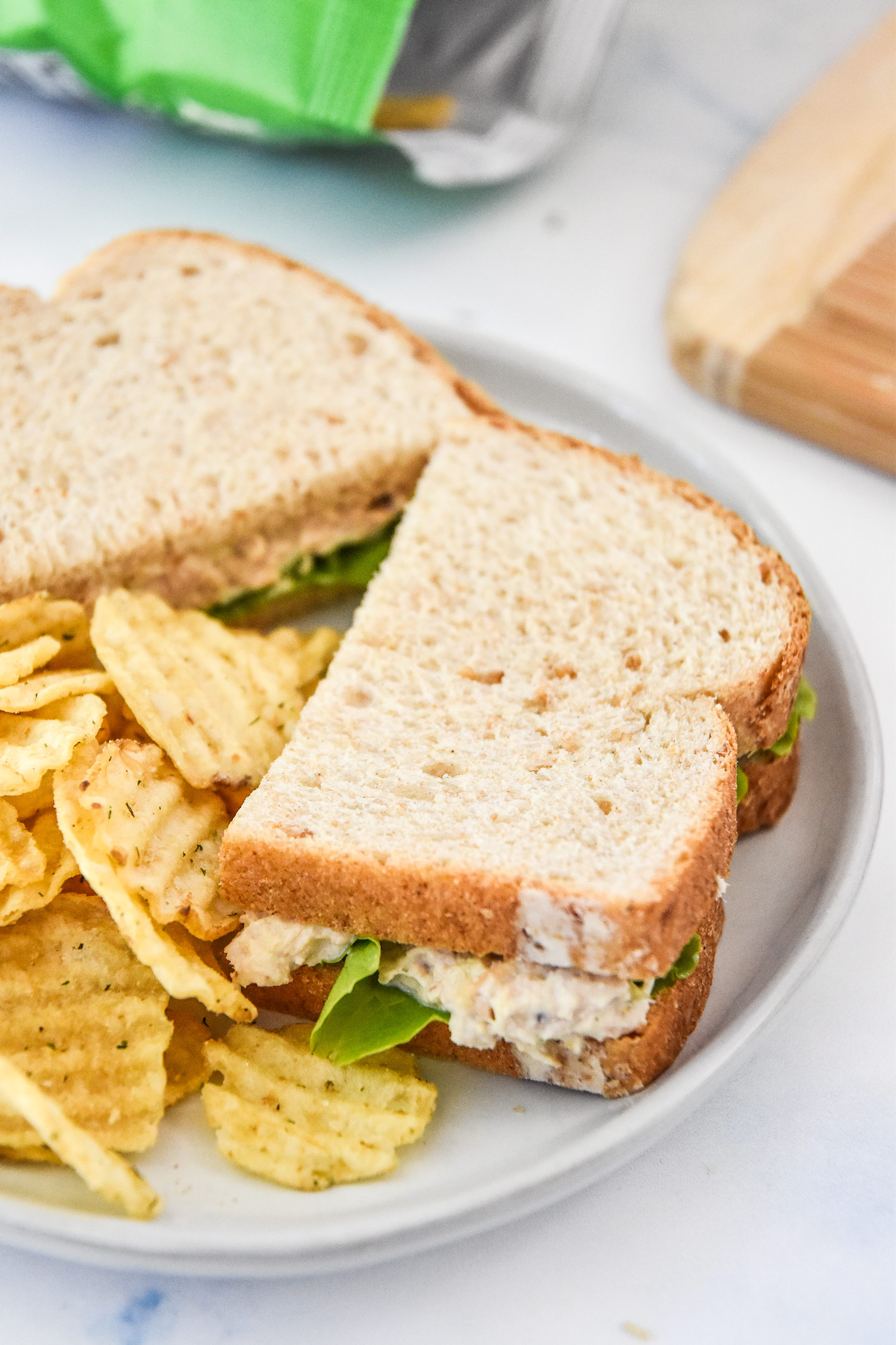 tuna salad sandwich with chips on a plate.
