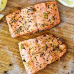 air fryer lemon pepper salmon filets on a cutting board.