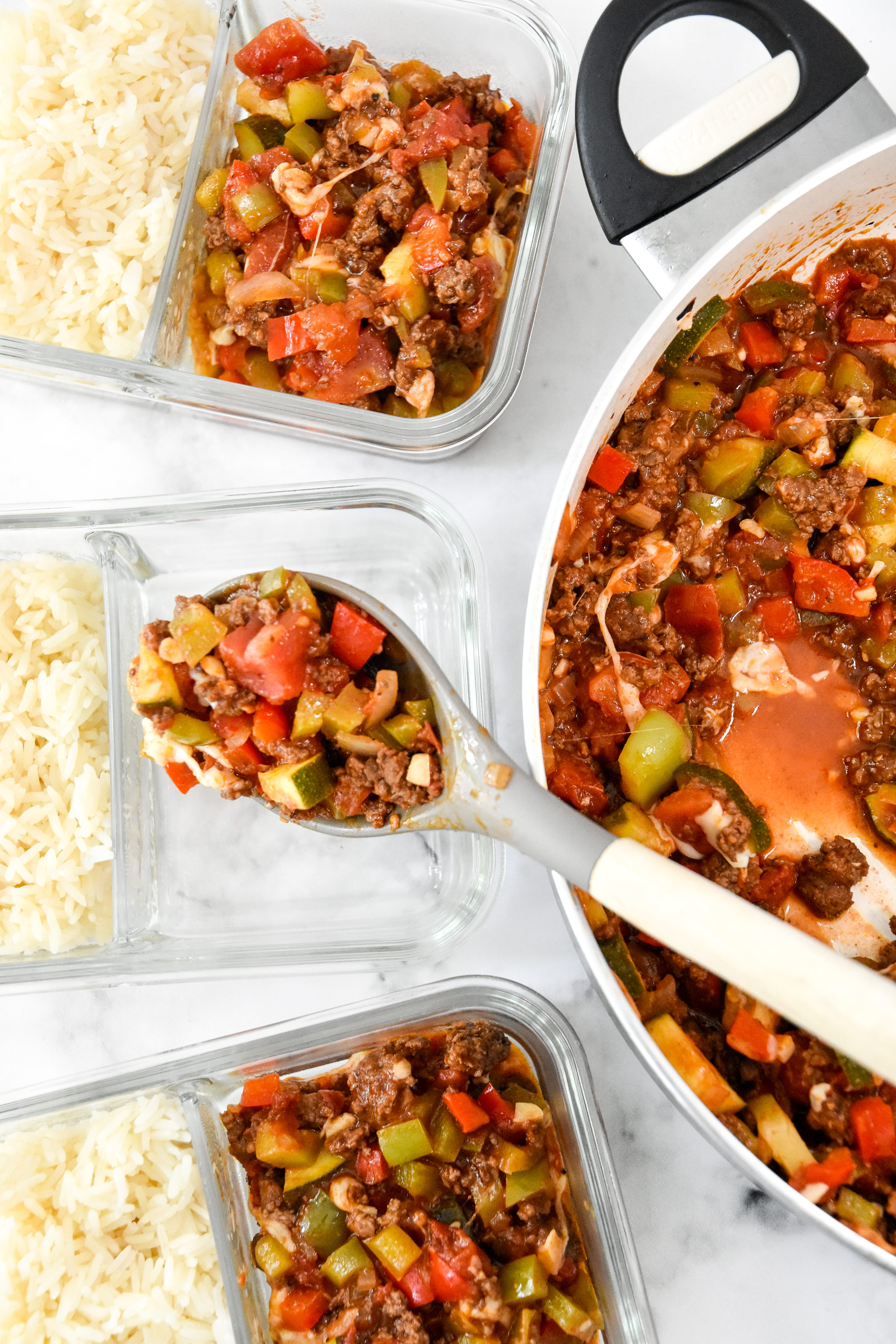 spooning unstuffed pepper mixture into the glass meal prep containers.